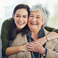 Portrait of a happy young woman spending time with her elderly relative at home