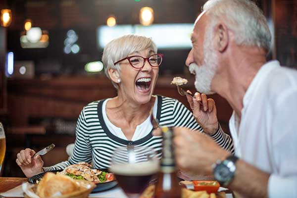 senior couple having dining and laughing