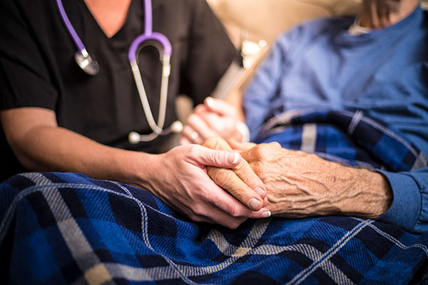 nurse holding elderly woman hands