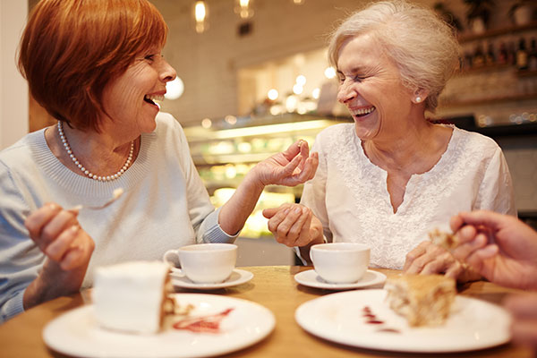 women laughing having desert