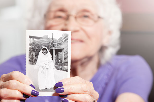 older woman holding black and white photo