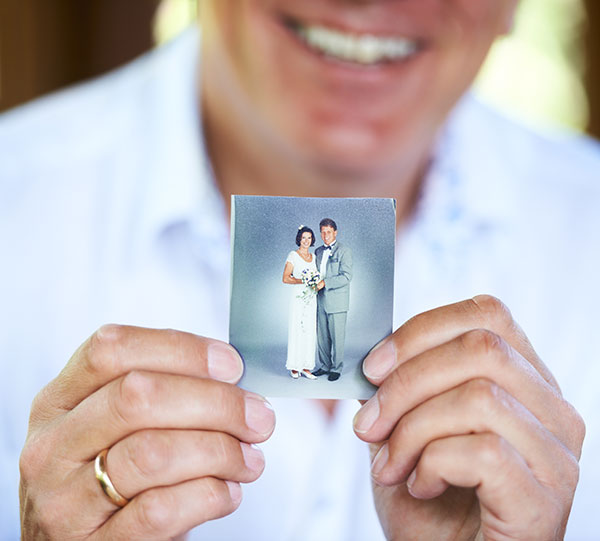 man holding photo of young couple