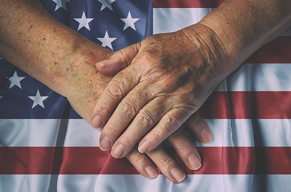 hands folded over american flag